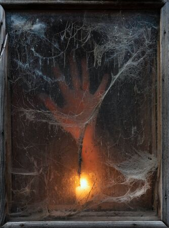 Terrible darkness. A spooky spider web in an old window. Hand of a ghost in the light of a candle