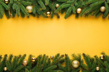 Yellow Christmas or New Year background. Decorative border of fir branches and Christmas balls. Stok Fotoğraf