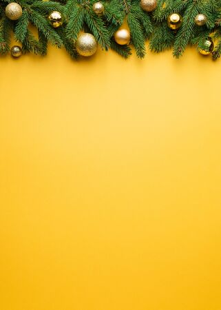Christmas and New Year yellow background. Decorative frame of fir branches and Christmas balls. Copy space for text