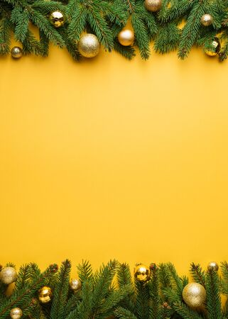 Christmas decoration border on yellow background. Fir Branches and Christmas Decorations