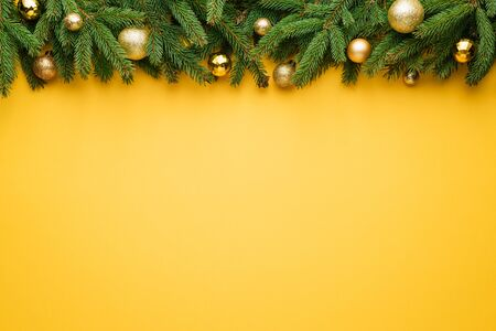 Yellow Christmas background. Decorative border of fir branches and Christmas balls. Copy space for text