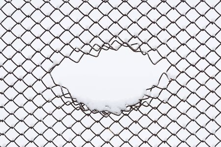Abstract winter background with copy space. Geometric pattern of a wire fence in the snow