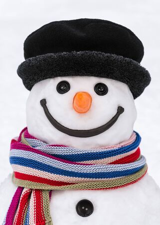 Face of a cute snowman with a kind smile. Traditional winter character made of snow. Merry christmas and happy new year card