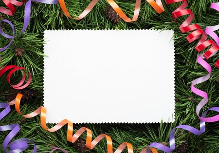 Christmas frame with pine decorated branches and a white paper sheet. Copy space for for holiday, congratulatory or advertising text