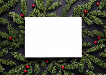 Merry Christmas and Happy New Year card. Note paper sheet wiht copy space. Decorative frame of fir branches and holly berries