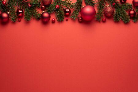 Rode achtergrond met kerstballen en Spar takken. Vrolijk kerstfeest of nieuwjaarsdecoratie met kopieerruimte