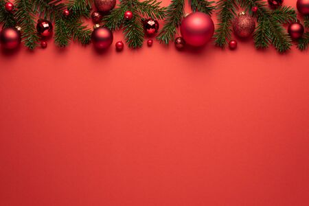Red background with Christmas balls and fir branches. Merry Christmas or New Year decoration with copy space Standard-Bild