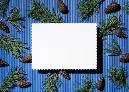 Happy holidays background with copy space for text. White note paper sheet on blue. pine branches and cones decoration Stok Fotoğraf