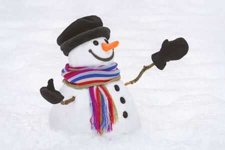 Cheerful snowman with a kind smile on a background of white snow. Good-natured Christmas character