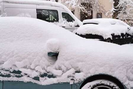 Sudden snowfall covered the streets of the city. Cars in the snow. Winter has come Stok Fotoğraf