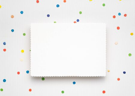 Light Christmas background with festive confetti. White paper sheet with copy space for text