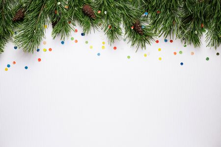 White Christmas and New Year background with pine branches and festive confetti