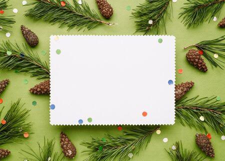 Christmas background with decor of pine branches and festive confetti. White sheet with a copy space for Christmas creep