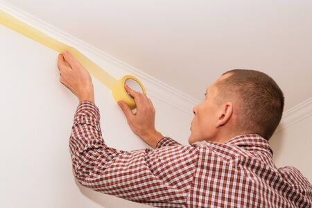 Home repairman prepares walls for painting. Masking ceiling masking tape