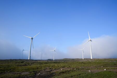 Wind turbines in fog. Blue background with copy space for text. Renewable energy