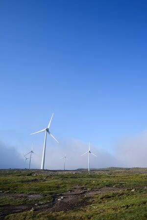 Renewable electricity. Wind power station on hill. Background with blue sky