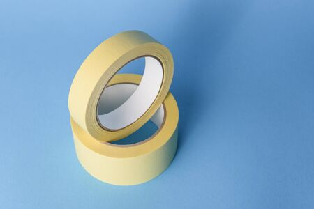 Yellow paper masking tape on a blue background for wall painting Archivio Fotografico