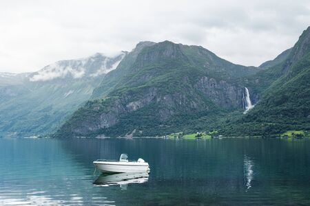 Norwegian landscape with a boat in the Lusterfjord fjord. Commune Luster, Norway. Mountain and waterfall view Archivio Fotografico