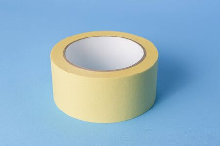 Masking tape for preparing the room before painting the walls. Paint tool (painter's tape) on a blue background