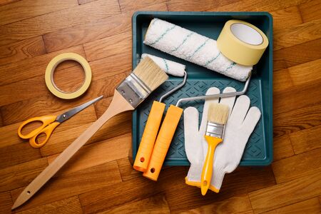 Set of tools for painting walls at home: painter's tape, gloves, scissors, paint rollers, tray and brush Archivio Fotografico