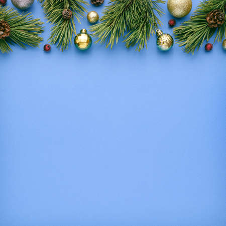 Square christmas card with fir decorations on blue background. Festive border with copy space for advertising text. Top view, flat lay Archivio Fotografico