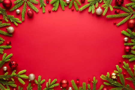 Red christmas background with oval frame. Happy holidays border with copy space for festive text. Top view, flat lay