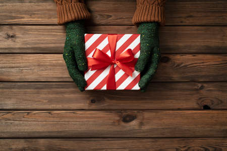 Exchange presents day. A box with a Christmas present in the hands of women