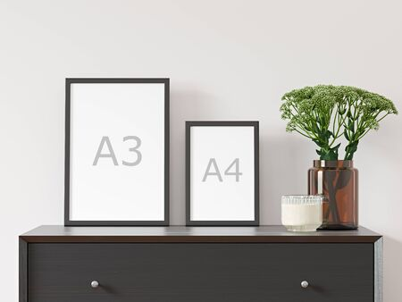 Two vertical empty A3 and A4 frames on white wall with black dresser, green plant in brown glass vase - close up image.