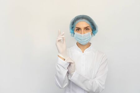 A female doctor in a medical mask puts white rubber gloves Banque d'images
