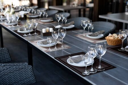 Festive table setting with empty wineglasses. Selebration banquet with brown napkins, plates and wineglasses for white and red wine on the wooden table 免版税图像