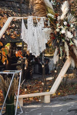 Wedding ceremony with arch in rustic style with macrame. Wedding exit ceremony with wood arch with fresh flowers and pampass grass Foto de archivo