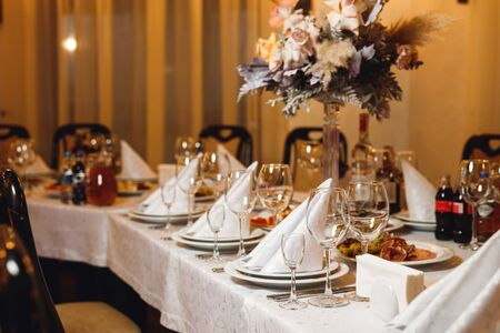 The table setting empty wineglasses on white tablecloth. Selebration banquet with white napkins, plates and wineglasses for white and red wine on the white table in restaurant