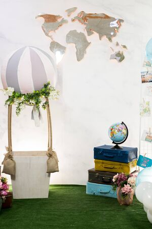 A stylish location for celebration photos with travel theme decoration. Isolated globe, air layer, vintage suitcases