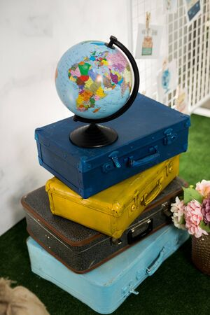 Travel or turism concept. Side view globe on vintage blue yellow brown suitcases