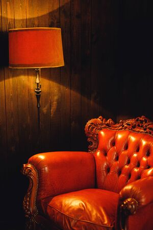 Photo shot details of modern brown armchair with brown lamp. Vintage armchair on dark wood background