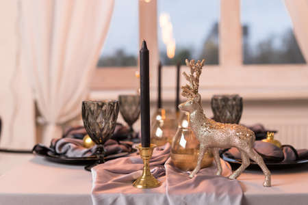 Close up of festive Christmas table setting with empty wine glasses and black plate with gold deer. Concept of Christmas and New Year