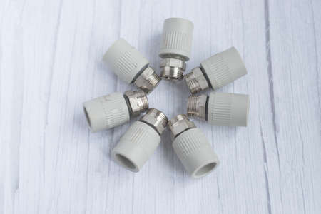 Combined couplings for connecting metal and polypropylene water pipes. Isolated nuts in circle in cold colors