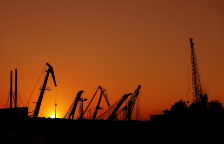 Silhouette of sea port cranes over sunset photo