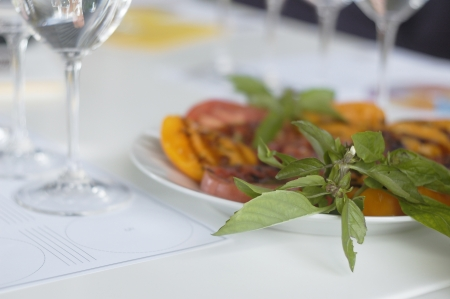 Closeup bunch of basil on plate of dishes with wine glass photo