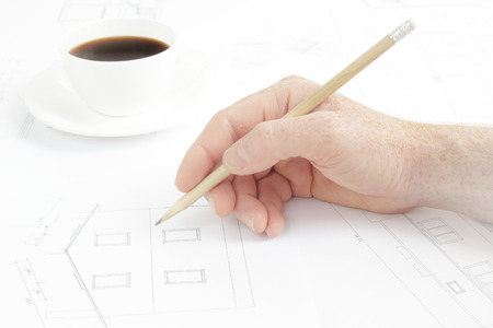 Architectural background  Human hand with pencil over blueprints with sketches of projects  photo