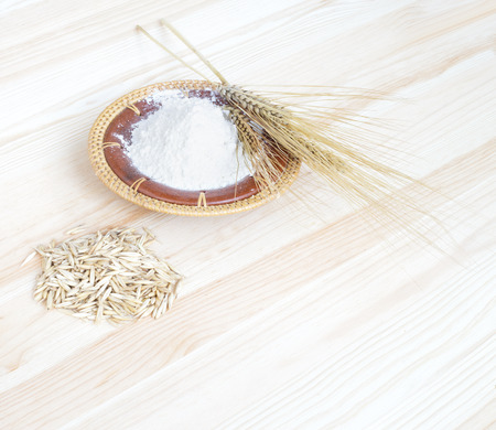 Oat flour with grains on the wooden table. photo