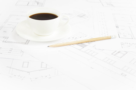 Architectural office desk with blueprints and coffe cup. photo