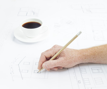 Architectural . Human hand with pencil over blueprints with sketches of projects. photo