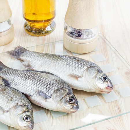 fish oil: Fresh fish for your menu with spices and oil bottle