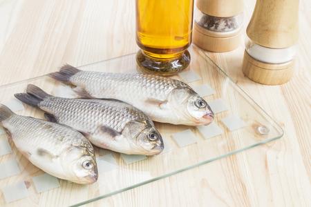 Pesce fresco per il menu con spezie e bottiglia di olio Archivio Fotografico - 29584190