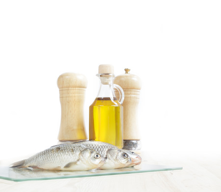 Fresh fish with spices and oil isolated over white  photo