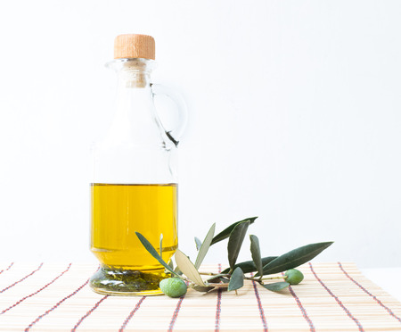 Glass bottle of olive oil and some olives with leaves isolated on a white background. photo