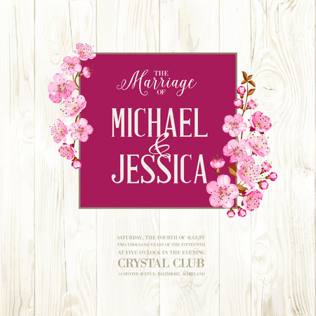 Wedding invitation on wooden backdrop. Spring flowers. Cherry blossom