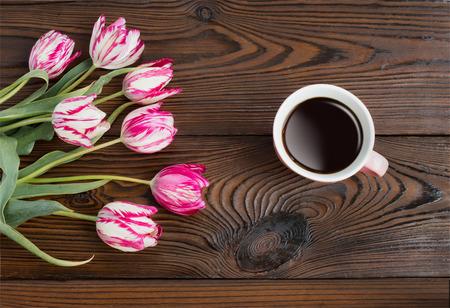planta de cafe: Taza de café con las flores del tulipán en el fondo de madera.