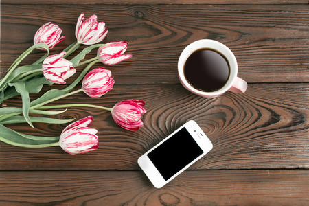 4s: SEVASTOPOL, UKRAINE - MAY 7, 2015: An iPhone 4S smartphone photographed on a wooden table with cup of coffee and spring flowers.